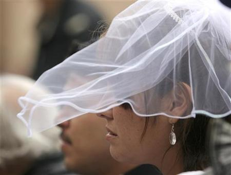 A bride's veil is blown by the wind during a mass marriage ceremony in Tijuana on Valentines Day February 14, 2008. REUTERS/Jorge Duenes