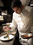 <p>Award-winning chef Michael Mina prepares a dish at the Bourbon Steak restaurant in Washington, in this undated handout. REUTERS/Mina Group/Handout</p>