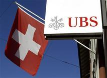 <p>Switzerland's national flag is seen beside the logo of Swiss bank UBS in front of a branch office in the town of Riehen near Basel September 30, 2011. REUTERS/Arnd Wiegmann</p>
