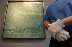 """<p>An art handler stands by """"Litzlberg on the Attersee"""" a painting by artist Gustav Klimt at Sotheby's Auction house in New York, October 19, 2011. A landscape painting by Austrian artist Gustav Klimt that had been stolen by the Nazis is expected to fetch more than $25 million when it is sold at auction next month, Sotheby's said. REUTERS/Brendan McDermid</p>"""
