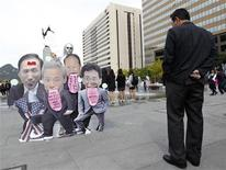 <p>A pedestrian (R) looks at artist Yang Eun-joo, 32, holding a solo protest denouncing the U.S.-South Korea free trade agreement talks in central Seoul October 21, 2011. REUTERS/Jo Yong-Hak</p>