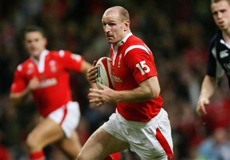 Wales captain Gareth Thomas (C) runs through to score a try against Scotland during their Six Nations rugby union match at the Millenium stadium in Cardiff February 12, 2006. REUTERS/Kieran Doherty