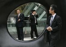 <p>A businessman (R) glances at other men through a work of outdoor art in Tokyo April 2, 2007. REUTERS/Toru Hanai</p>