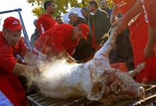 <p>Competitors clean a slaughtered pig which will be used to make sausages during Europe's biggest sausage festival in Bekescsaba, 240 km (149 miles) southeast of Budapest, October 29, 2011. REUTERS/Laszlo Balogh</p>