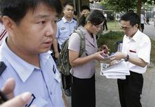 <p>Yuan Weijung (C), the wife of blind Chinese activist Chen Guangcheng, who is serving a four-year prison term after exposing forced abortions and sterilisation in northern China in 2005, is checked by uniformed and plainclothes policemen as she leaves her home in Beijing August 24, 2007. REUTERS/Reinhard Krause</p>