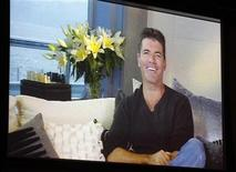 <p>Simon Cowell, one of the judges on new reality series 'The X Factor' is shown on a large screen as he speaks via satellite from England, during a panel session at the FOX Summer TCA Press Tour in Beverly Hills, California August 5, 2011. REUTERS/Fred Prouser</p>