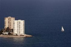 <p>A boat sails past buildings at the coast line of Cullera near Valencia March 27, 2009. REUTERS/Heino Kalis</p>