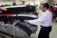<p>An Indonesian baggage handler pushes a trolley full of surf boards to be loaded onto an Australia-bound Quantas flight at Denpasar airport on the Indonesian resort island of Bali, October 14, 2002. REUTERS/Darren Whiteside</p>