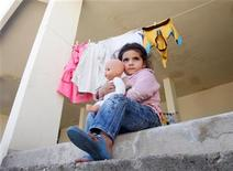 <p>A Syrian refugee girl carries a doll that she received from a women's non-profit charity organization on the first day of Eid al-Adha, at an abandoned school in Wadi Khaled area, northern Lebanon, November 6, 2011. REUTERS/ Omar Ibrahim</p>