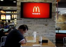 <p>Customer Steven Price sits at a table near a HDTV screen showing the new McDonald's Channel featuring a commerical about McCafe drinks at a McDonald's restaurant, part of the test market for the channel in Norwalk, California October 17, 2011. REUTERS/Fred Prouser</p>