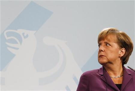 German Chancellor Angela Merkel listens to Turkish Prime Minister Tayyip Erdogan as they address the media after meeting in the Chancellery in Berlin November 2, 2011. REUTERS/Fabrizio Bensch