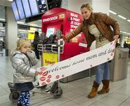 <p>Two-year-old Luna (L) and her aunt hold a banner at Amsterdam Airport Schiphol November 24, 2011. REUTERS/Paul Vreeker/United Photos</p>