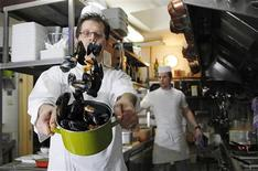 <p>Cook Lavdim Kelmendi shakes a pot of mussels at the Volle Gas restaurant in Brussels November 24, 2011. REUTERS/Francois Lenoir</p>