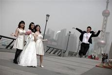 <p>A wedding party pose for pictures with the Oriental Pearl TV Tower in the background on a hazy day in Shanghai in this May 3, 2011 file photo. REUTERS/Carlos Barria/Files</p>