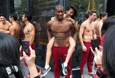 <p>A woman poses for photographs with a shirtless model outside a department store in Singapore's Orchard Road shopping district December 14, 2011. REUTERS/Claro Cortes IV</p>