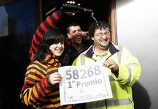 """<p>People celebrate having one of the winning tickets as they show a facsimile of the winning lottery number in Spain's Christmas Lottery """"El Gordo"""" in Granen, northern Spain, December 22, 2011. REUTERS/Luis Correas</p>"""