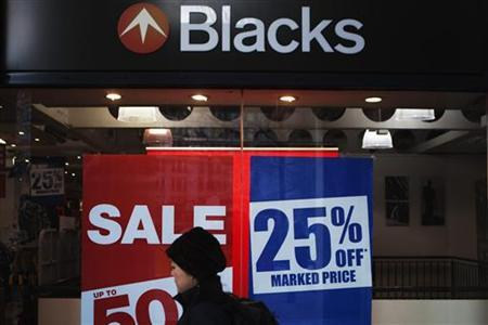 A pedestrian walks past British outdoor equipment retailer Blacks display window with signs announcing signs in London, December 16, 2011. REUTERS/Finbarr O'Reilly