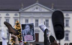 """<p>People hold up shoes and a placard during a protest demanding German President Christian Wulff resign outside the presidential palace, Bellevue Castle, in Berlin, January 7, 2012. German President Christian Wulff refused earlier this week to approve the publication of a potentially explosive voicemail message he left on the phone of a top newspaper editor, in an escalating scandal that could cost him his job and damage Chancellor Angela Merkel. The placard reads: """"This office requires talent: (German comedian) Georg Schramm for president!"""" REUTERS/Thomas Peter</p>"""
