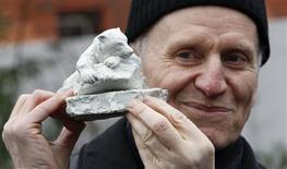 """<p>Sculptor Josef Tabachnyk, poses for the media in front of the polar bear enclosure at the Zoo in Berlin, January 17, 2012, with his design, """"Knut - The Dreamer"""", which was chosen out of more than 40 proposals to become a memorial for the late polar bear Knut. REUTERS/Fabrizio Bensch</p>"""