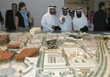 <p>Emirati citizens look at a model of Al Saadiyat Island, on which the Louvre Abu Dhabi will be built, during the signing of a cultural exchange agreement in Abu Dhabi March 6, 2007. REUTERS/Osayd Hasan</p>