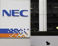 <p>A woman walks near a signboard of NEC Corp in Tokyo January 26, 2012. REUTERS/Toru Hanai</p>
