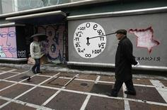 <p>People walk in front of a closed shop with graffiti on it in central Athens January 24, 2012. REUTERS/John Kolesidis</p>