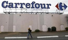 <p>A woman walks below the logo of Carrefour Planet supermarket in Bordeaux, southwestern France, January 19, 2012. REUTERS/Regis Duvignau</p>