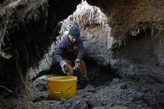 <p>Jozsef Bari, 52, digs for coal by hand from a spoil bank next to a defunct coal mine near Farkaslyuk (200 km northeast of Budapest) February 2, 2012. Bari and many others from Farkaslyuk, a town stricken hard by unemployment and dire poverty, keep warm during freezing temperatures of -17 degrees Celsius with the coal. The spoil bank is owned by a private company, which turns a blind eye on the theft so as to spare the coal diggers from the cold. REUTERS/Laszlo Balogh</p>