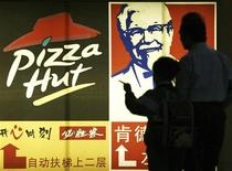 <p>People stand in front of a poster of KFC and Pizza Hut in Guangzhou, capital of south China's Guangdong province in this April 2, 2007 file photo. REUTERS/Joe Tan/Files</p>