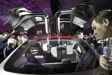 <p>People look at the Tesla Motors Model X electric vehicle at its unveiling at the Tesla Design Studio in Hawthorne, California February 9, 2012. REUTERS/David McNew</p>