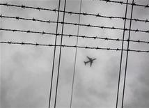 <p>An airplane flies through low cloud above high tension electricity transmission cables and barbed wire in Sydney November 24, 2009.REUTERS/Tim Wimborne</p>