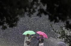 <p>Women chat with each other as they protect themselves from the falling snow with umbrellas in front of Rome's ancient Colosseum February 3, 2012. REUTERS/Alessandro Bianchi</p>