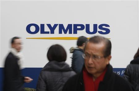 People walk past a signboard of Olympus Corp outside its showroom in Tokyo February 16, 2012. REUTERS/Issei Kato