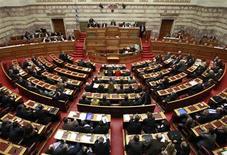 <p>Les députés grecs ont adopté mardi soir un train de mesures d'austérité prévoyant de nouvelles coupes dans les salaires et les retraites, tel que le réclament les bailleurs internationaux en échange du nouveau plan d'aide de 130 milliards d'euros. /Photo prise le 28 février 2012/REUTERS/John Kolesidis</p>