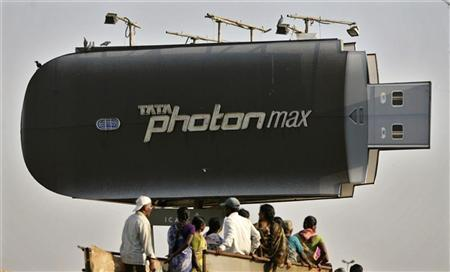 People travel in a truck under a large advertisement of Tata's wireless internet device in the southern Indian city of Hyderabad March 1, 2012. REUTERS/Krishnendu Halder