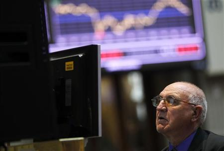 A trader looks at screens during trading at the Madrid bourse April 19, 2012. REUTERS/Susana Vera