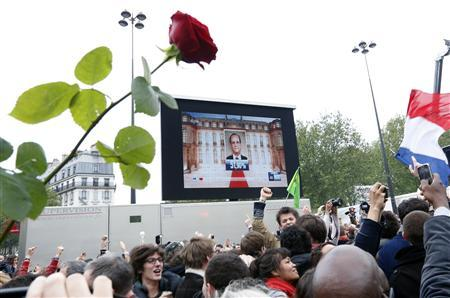 The face of the newly-elected French President Francois Hollande appears on a giant screen to announce the winner of the 2012 French presidential elections as Socialist supporters react at La Bastille square in Paris May 6, 2012. REUTERS/Pascal Rossignol