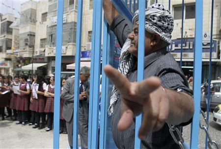 A Palestinian man gestures from inside a mock prison cell during a rally in the West Bank city of Ramallah, in support of Palestinian prisoners on a hunger strike in Israeli jails May 14, 2012. REUTERS/Mohamad Torokman