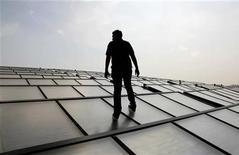 <p>Un ingénieur sur un panneau photovoltaïque. Selon une étude sur la pénurie de compétences, les économies des pays développés souffrent d'un déficit persistant de travailleurs qualifiés et d'ingénieurs et les employeurs préfèrent laisser les postes vacants plutôt que d'embaucher un travailleur qui ne convient pas. /Photo d'archives/REUTERS/Tim Chong</p>