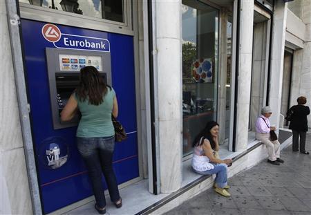 A woman (L) makes a transaction at an ATM machine outside a Eurobank branch in central Athens May 30, 2012. REUTERS/John Kolesidis