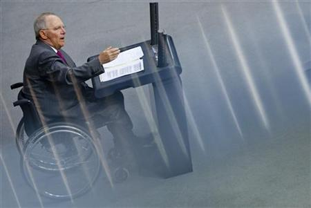 German Finance Minister Wolfgang Schaeuble speaks during a debate of the Bundestag, the lower house of parliament, about the European Fiscal Compact in Berlin March 29, 2012. The streaks in the picture were created by reflections in a metal railing. REUTERS/Thomas Peter