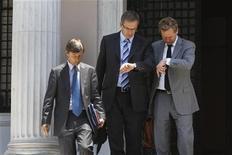 """<p>Représentants du Fonds monétaire international, de la Banque centrale européenne quittant les bureaux du Premier ministre grec Antonis Samaras, début juillet, à Athènes. La Grèce va relancer son programme de mise """"en réserve"""" destiné à renvoyer à terme 40.000 fonctionnaires afin de réaliser les 11,5 milliards d'euros d'économies auxquelles elle s'est engagée auprès de l'Union européenne et du FMI. /Photo prise le 5 juillet 2012/REUTERS/John Kolesidis</p>"""