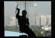 <p>Un trabajador limpia una ventana de un edificio de departamentos en Pekín, oct 24 2012. Un índice privado sobre el sector servicios de China cayó en octubre y una debilidad mayor que la prevista en los nuevos pedidos inyectó una nota de precaución después de que tres sondeos anteriores para octubre mostraron que la segunda mayor economía del mundo está recuperando su impulso. REUTERS/Petar Kujundzic</p>