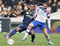 <p>Le Lyonnais Lisandro Lopez (ç droite) aux prises avec Odair Fortes de Reims, sur la pelouse du stade Gerland. L'OL a pris provisoirement les commandes de la Ligue 1 à la faveur d'une nette victoire 3-0. /Photo prise le 18 novembre 2012/REUTERS/Robert Pratta</p>