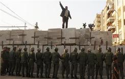 <p>Protestation près du palais présidentiel au Caire. Le principal groupe d'opposition au président égyptien Mohamed Morsi a annoncé dimanche qu'il rejetait le référendum constitutionnel prévu le 15 décembre par le chef de l'Etat, disant craindre une confrontation violente dans le pays et a appelé à de nouvelles manifestations. /Photo prise le 9 décembre 2012/REUTERS/Asmaa Waguih</p>