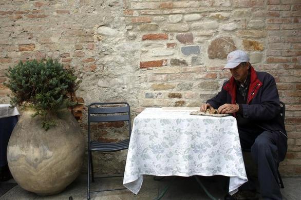 66岁的松露猎人Ezio Costa在2013年11月9日在意大利西北部Alba附近Monchiero的餐厅外面检查松露.REUTERS-Stefano Rellandini