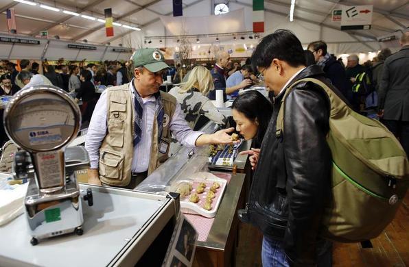2013年11月9日,卖家在意大利西北部阿尔巴的松露市场向消费者展示松露.REUTERS-Stefano Rellandini