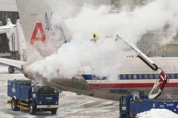 2014年1月2日,一名美国航空公司的机组人员在波士顿冬季的夜间暴风雪中喷洒除冰解决方案.REUTERS-Dominick Reuter