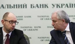 Le Premier ministre ukrainien, Arseni Iatseniouk (à gauche), ici aux côtés du gouverneur de la banque centrale ukrainnienne Stepan Kubiv, a déclaré que Kiev espérait commencer à recevoir sous peu une aide internationale et que l'Ukraine était décidée à remplir les conditions exigées pour obtenir l'appui du Fonds monétaire international (FMI). /Photo prise le 28 février 2014/REUTERS/Konstantin Chernichkin