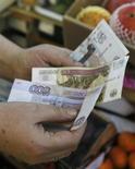 Продавщица пересчитывает рублевые купюры на рынке в Москве 3 марта 2014 года. Рубль незначительно подрос утром вторника в начале апрельского налогового периода, оставаясь вблизи трехнедельных минимумов из-за напряженной ситуации на востоке Украины и связанных с нею возможных рисков для России. REUTERS/Maxim Shemetov